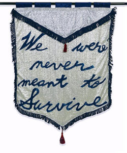"two banners, one embroidered with ""We were never meant to survive"" and the other depicting an eagle stabbed with a pencil soaring over two guns"